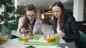 Madre e hija un adolescente en un café que come los tallarines y hablar metrajes