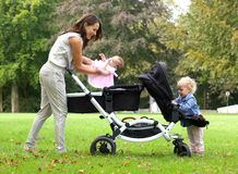 Madre e hijas con el cochecito de niño al aire libre Foto de archivo libre de regalías