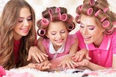 Madre e hijas en bigudíes de pelo Imágenes de archivo libres de regalías