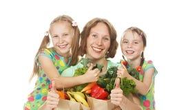 Madre e hijas felices de la familia con los bolsos de verduras foto de archivo