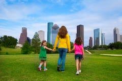 Madre e hijas que caminan llevando a cabo las manos en horizonte de la ciudad Fotos de archivo libres de regalías