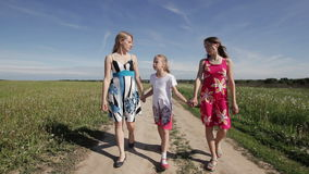 Madre e hijas que caminan llevando a cabo sus manos almacen de video