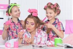 Madre e hijas que hacen peinados fotografía de archivo