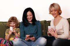 Madre e hijas que juegan con los teléfonos y la tablilla elegantes Fotografía de archivo