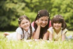Madre e hijas que mienten al aire libre con las flores Imagenes de archivo