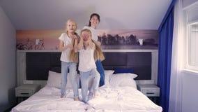 Madre e hijas que saltan en cama almacen de metraje de vídeo