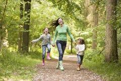 Madre e hijas que saltan en la sonrisa del camino Foto de archivo