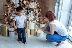 Madre e hijo cerca de un árbol de navidad Fotografía de archivo libre de regalías
