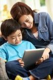 Madre e hijo chinos que usa el ordenador de la tablilla Foto de archivo libre de regalías