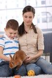 Madre e hijo con el animal doméstico del conejito Imagen de archivo