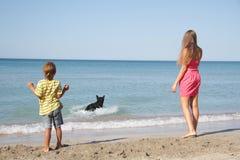 Madre e hijo con el perro en la playa Imagen de archivo