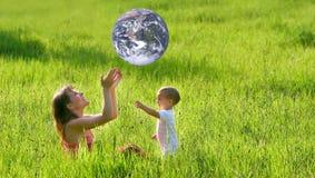 Madre e hijo con la bola earth-like imagen de archivo libre de regalías