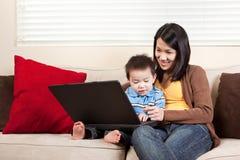 Madre e hijo con la computadora portátil imagenes de archivo