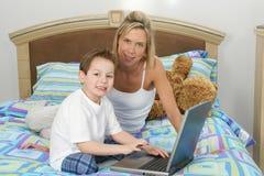 Madre e hijo con la computadora portátil en cama fotografía de archivo