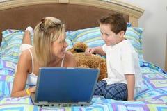 Madre e hijo con la computadora portátil en cama foto de archivo libre de regalías