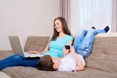 Madre e hijo con un ordenador portátil con un teléfono en el sofá en casa Fotografía de archivo libre de regalías