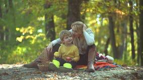 Madre e hijo de los niños que se divierte y que juega en la naturaleza del otoño Aire libre feliz de la mamá y del hijo Familia f almacen de metraje de vídeo