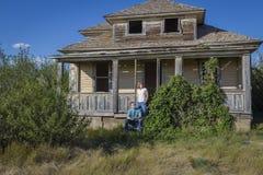 Madre e hijo delante de una casa abandonada Imagen de archivo libre de regalías