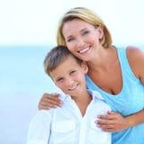 Madre e hijo en abrazo en la playa Fotos de archivo libres de regalías