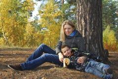 Madre e hijo en bosque del otoño. Imagen de archivo