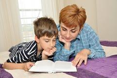 Madre e hijo en cama que leen un libro Foto de archivo