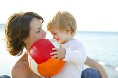 Madre e hijo en el mar, bola del balompié Foto de archivo libre de regalías