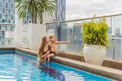 Madre e hijo en la piscina entre los rascacielos y la ciudad grande Relájese en la ciudad grande Resto de la tensión fotos de archivo