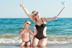 Madre e hijo en los bañadores y las gafas de sol que toman un selfie en un teléfono móvil en la costa de mar foto de archivo
