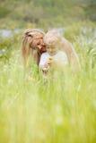 Madre e hijo en prado verde fotos de archivo