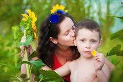 Madre e hijo en un campo de girasoles en verano Foto de archivo libre de regalías