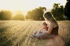 Madre e hijo en un campo de la cosecha Imagenes de archivo