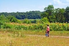 Madre e hijo en un prado de la flor Foto de archivo libre de regalías