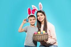 Madre e hijo en vendas de los o?dos del conejito con la cesta de huevos de Pascua en color fotos de archivo