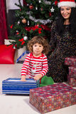 Madre e hijo felices debajo del árbol de navidad Fotos de archivo