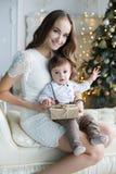Madre e hijo joven en casa cerca del árbol de navidad Foto de archivo