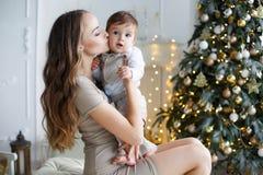 Madre e hijo joven en casa cerca del árbol de navidad Foto de archivo libre de regalías