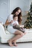 Madre e hijo joven en casa cerca del árbol de navidad Fotografía de archivo libre de regalías