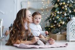 Madre e hijo joven en casa cerca del árbol de navidad Fotografía de archivo