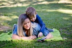 Madre e hijo joven que ponen en la manta en parque usando el teléfono elegante Imagen de archivo