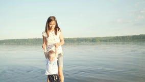 Madre e hijo jovenes en la playa Una muchacha tuerce alrededor ella misma a un pequeño hijo que lleva a cabo las manos almacen de video