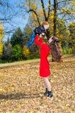 Madre e hijo jovenes en parque del otoño familia feliz: el juego del muchacho de la madre y del niño que abraza el otoño camina e Foto de archivo