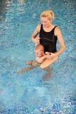 Madre e hijo jovenes en una piscina Foto de archivo
