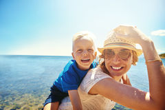 Madre e hijo jovenes felices en una playa tropical Foto de archivo