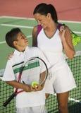 Madre e hijo por la red en la opinión de alto ángulo del campo de tenis Fotografía de archivo