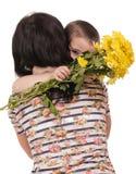 Madre e hijo que abrazan con las flores Foto de archivo libre de regalías