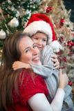 Madre e hijo que abrazan en la Navidad Fotos de archivo libres de regalías