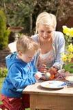 Madre e hijo que adornan los huevos de Pascua Fotografía de archivo libre de regalías