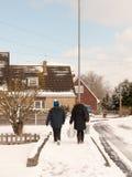 Madre e hijo que caminan abajo de la calle con nieve en estado de Reino Unido del invierno Fotografía de archivo libre de regalías