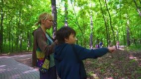 Madre e hijo que caminan en parque y que miran con binocular el d?a de primavera metrajes