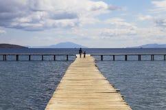 Madre e hijo que caminan en un fondo de madera del embarcadero con el cielo azul Imagen de archivo